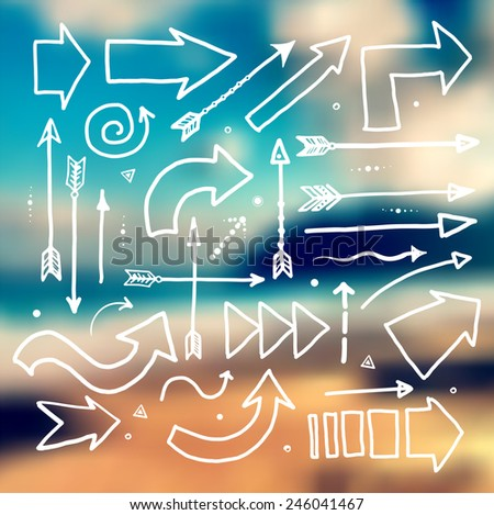 Set of white doodle sketch arrows on blurred background with seashore. Vector illustration. - stock vector