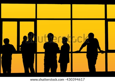 Silhouette of airline passengers in an airport lounge at the wide observation window watching an airplane flying of against a surreal sunset in the horizon with direction signage in the foreground. - stock vector