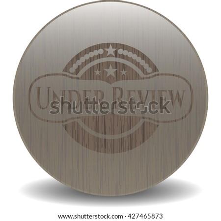 Under Review vintage wood emblem - stock vector