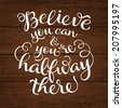 """Vector calligraphic inscription with ornamental elements on wood background. """"Believe you can and you're halfway there"""" poster or postcard. Typography collection - stock vector"""