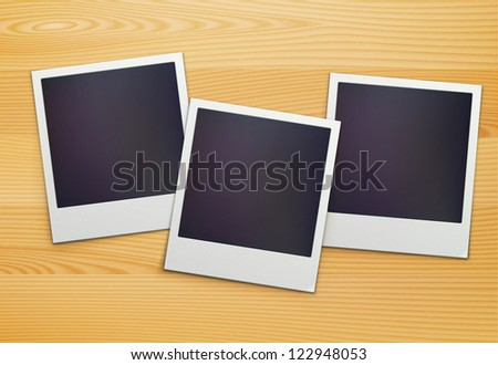 Vector illustration of three blank retro polaroid photo frames over wooden background - stock vector